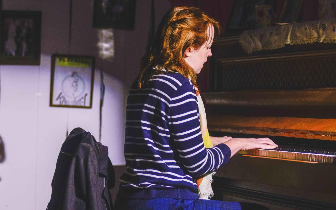 Victoria Brazier playing the piano in Crossings by Deirdre Kinahan